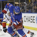 Calgary Flames' Mark Giordano (5) defends New York Rangers' Carl Hagelin (62) during the second period of an NHL hockey game Tuesday, Feb. 24, 2015, in New York. (AP Photo/Frank Franklin II)