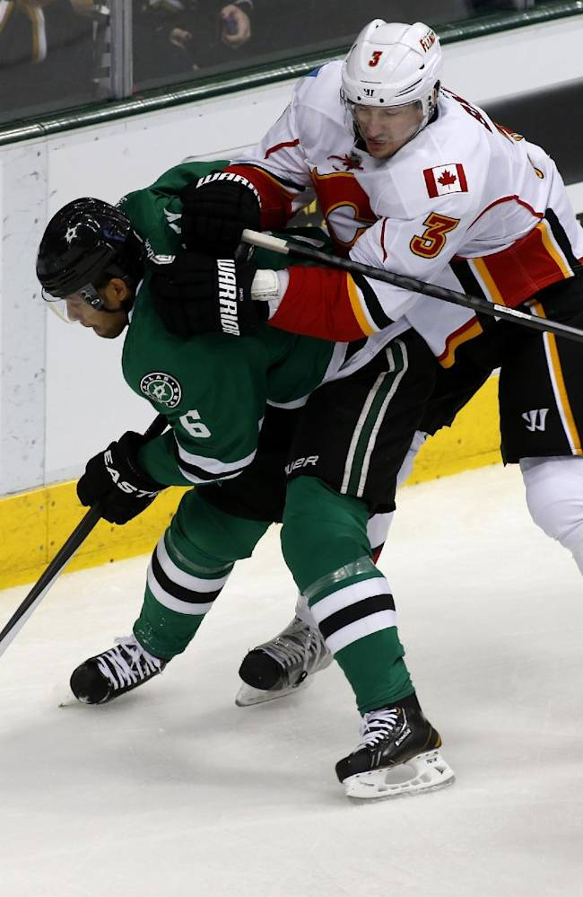 Dallas Stars defenseman Trevor Daley (6) and Calgary Flames defenseman Ladislav Smid (3), of Russia, fight for the puck in the first period of an NHL hockey game Friday, March 14, 2014, in Dallas