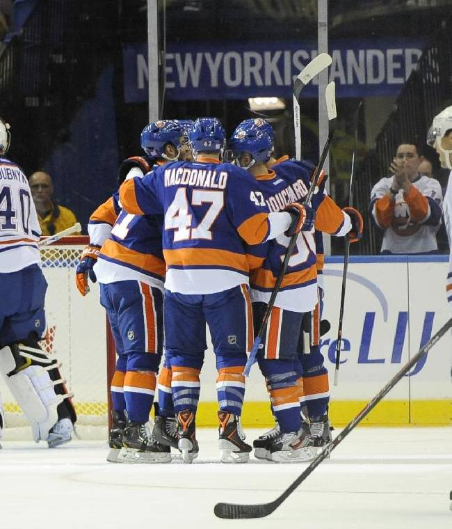 New York Islanders' Andrew MacDonald (47), Pierre-Marc Bouchard (96) and teammates celebrate Josh Bailey's goal against Edmonton Oilers goalie Devan Dubnyk (40) as Jordan Eberle (14) reacts in the first period of an NHL hockey game on Thursday, Oct. 17, 2013, in Uniondale, N.Y