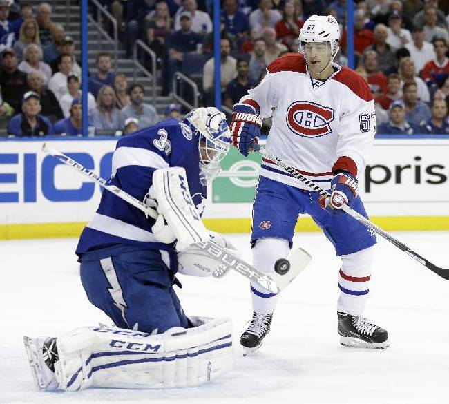 Tampa Bay Lightning goalie Anders Lindback (39), of Sweden, makes a stick-save as Montreal Canadiens left wing Max Pacioretty (67) looks for a rebound on a shot during the first period of Game 1 of a first-round NHL hockey playoff series on Wednesday, April 16, 2014, in Tampa, Fla