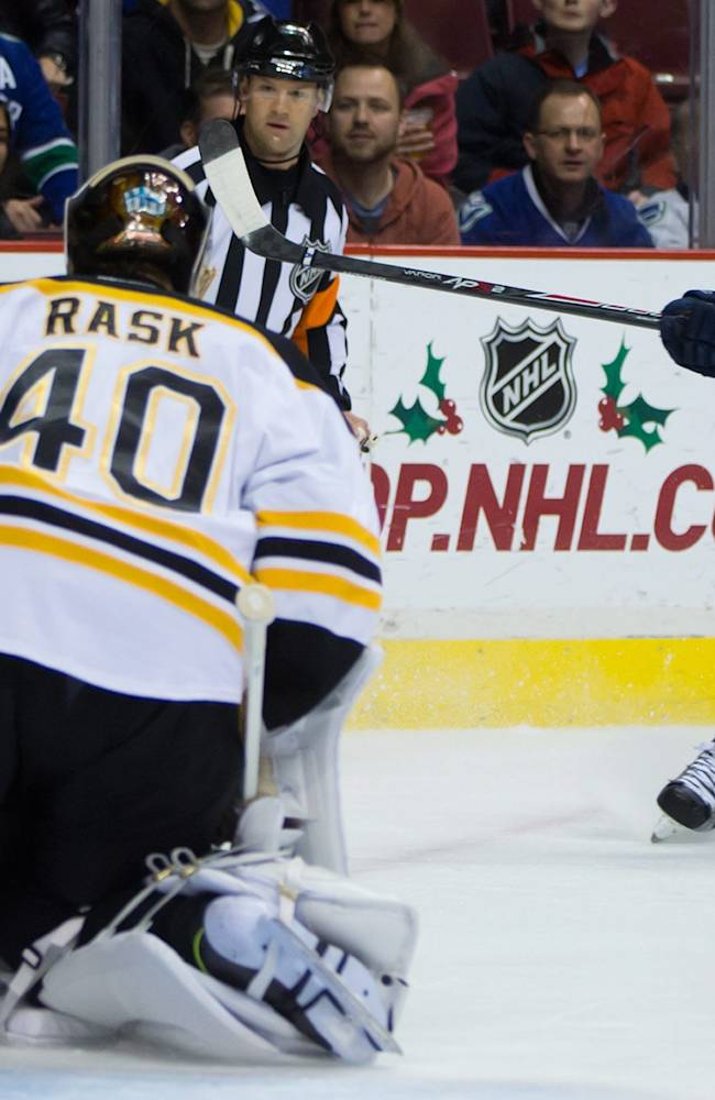 Vancouver Canucks' Mike Santorelli's shot gets past Boston Bruins' goalie Tuukka Rask, of Finland, but stays out of the net during first period NHL hockey action in Vancouver, British Columbia, on Saturday, Dec. 14, 2013