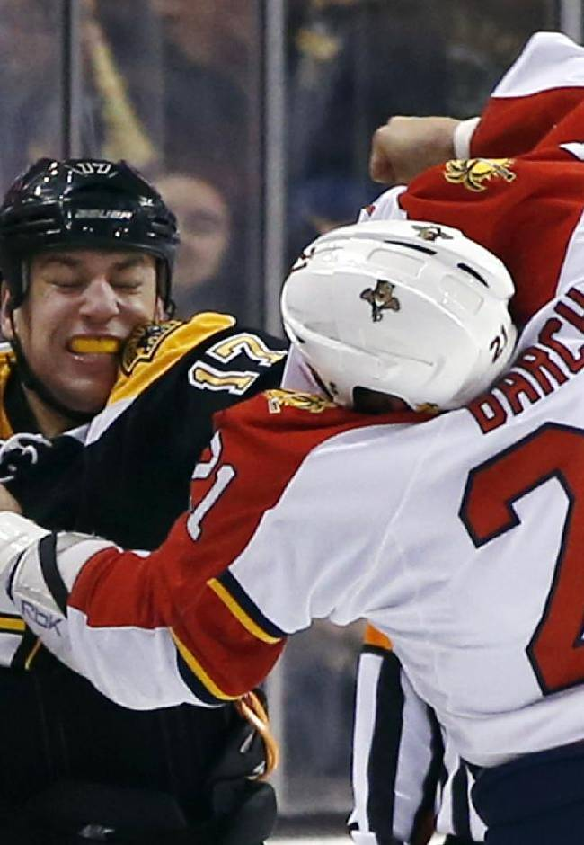 Boston Bruins left wing Milan Lucic (17) and Florida Panthers right wing Krys Barch (21) fight during the first period of an NHL hockey game in Boston, Tuesday, March 4, 2014