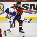 Edmonton Oilers' Jordan Eberle, left, gets knocked to the ice by Calgary Flames' Dennis Wideman during second period NHL hockey action in Calgary, Alberta The Associated Press