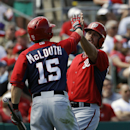Washington Nationals' Brock Peterson, right, high-fives teammate Nate McLouth after Peterson scored off a single by Jamey Carroll in the third inning of an exhibition spring training baseball game against the St. Louis Cardinals, Saturday, March 8, 2014,