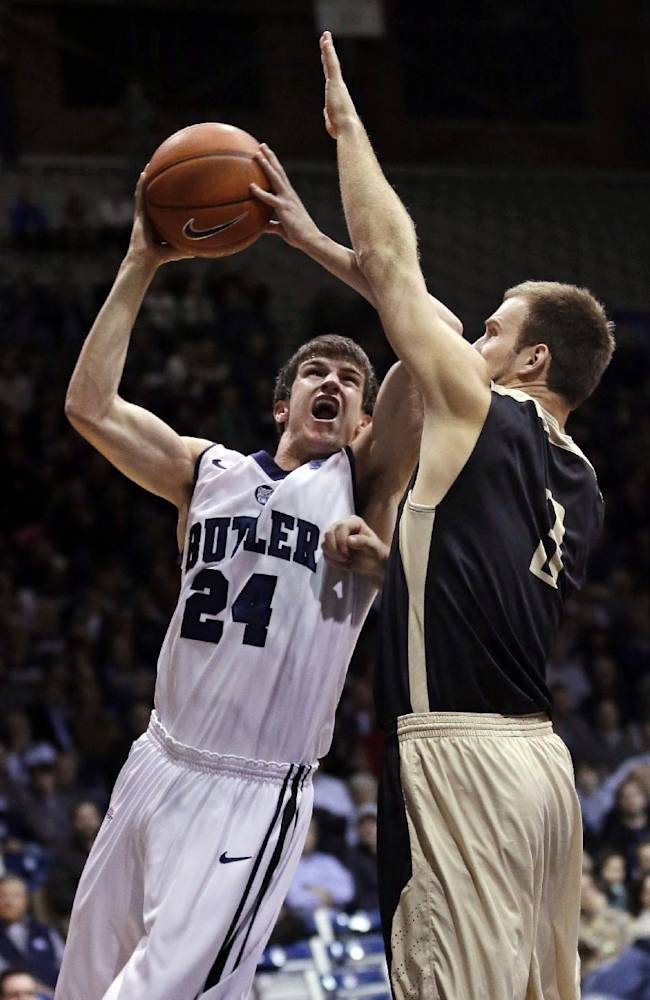Butler guard Kellen Dunham, left, shoots over Manchester guard Silas Sims in the first half of an NCAA college basketball game in Indianapolis, Monday, Dec. 9, 2013