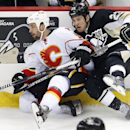 Calgary Flames' Deryk Engelland, left, collides with Pittsburgh Penguins' Steve Downie (23) during the third period of an NHL hockey game in Pittsburgh, Friday, Dec. 12, 2014. The Penguins won 3-1 The Associated Press
