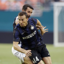 Juventus forward Mirko Vucinic, right, challenges Inter Milan defender Hugo Campagnaro (14) for the ball during the first half of an International Champions Cup soccer game, Tuesday, Aug. 6, 2013, in Miami. (AP Photo/Wilfredo Lee)
