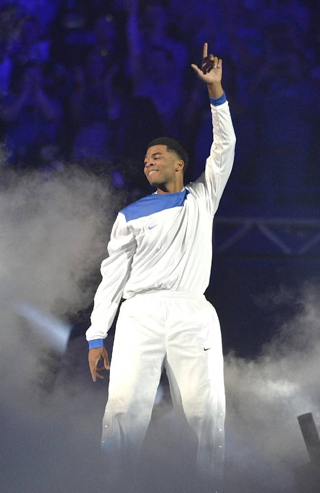 Kentucky freshman Andrew Harrison shows his appreciation to the crowd during his introduction before the start of Kentucky's Big Blue Madness scrimmage Friday, Oct. 18, 2013 in Lexington, Ky