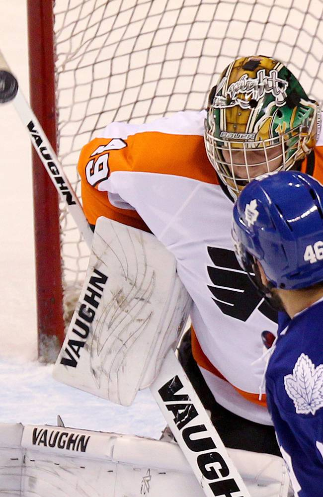 Toronto Maple Leafs' David Broll watches the puck directed at Philadelphia Flyers' goalie Anthony Stolarz during the second period of an NHL pre-season game, Sunday Sept. 15, 2013 in London, Ontario