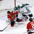 Chicago Blackhawks center Andrew Shaw (65) shoots and scores past Dallas Stars goalie Kari Lehtonen (32), and Trevor Daley (6) as teammate Duncan Keith watches during the first period of an NHL hockey game Tuesday, March 25, 2014, in Chicago The Associate