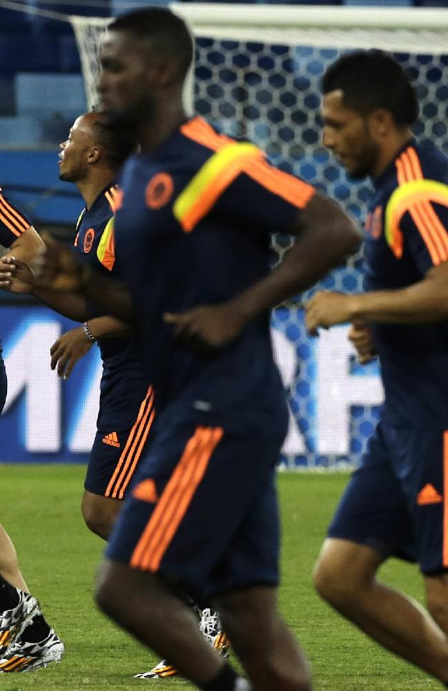 Colombia's James Rodriguez, left, and teammates warm up during a training session of Colombia at Arena Pantanal in Cuiaba, Brazil, Monday, June 23, 2014.  Colombia play in group C of the 2014 soccer World Cup
