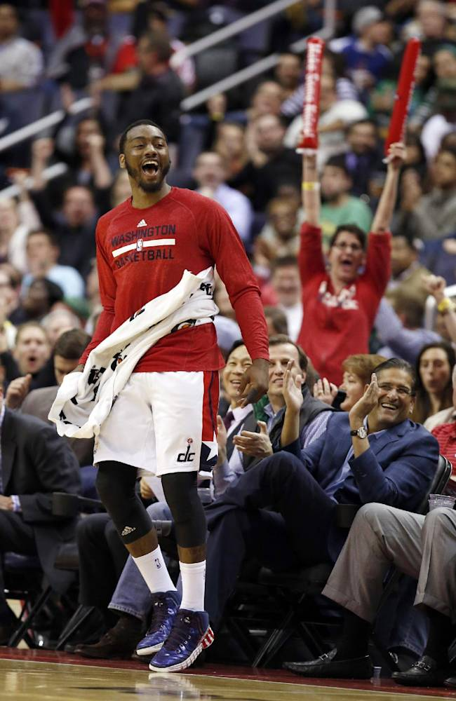 Washington Wizards guard John Wall, left, celebrates near the bench during the second half of an NBA basketball game against the Boston Celtics on Wednesday, April 2, 2014 in Washington. The Wizards won 118-92, and clinched a playoff berth