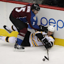Boston Bruins center Gregory Campbell (11) reaches for the puck as Colorado Avalanche defenseman Nate Guenin (5) covers him in the third period of an NHL hockey game in Denver on Friday, March 21, 2014. Boston won 2-0 The Associated Press