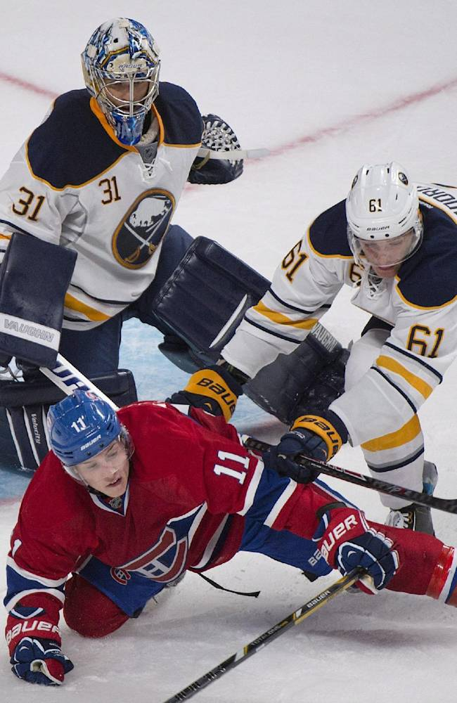 Montreal Canadiens' Brendan Gallagher (11) is pushed over by Buffalo Sabres' Nikita Zadorov (61) as Sabres' goaltender Matt Hackett looks on during third period NHL pre-season hockey action in Montreal, Sunday, Sept. 15, 2013