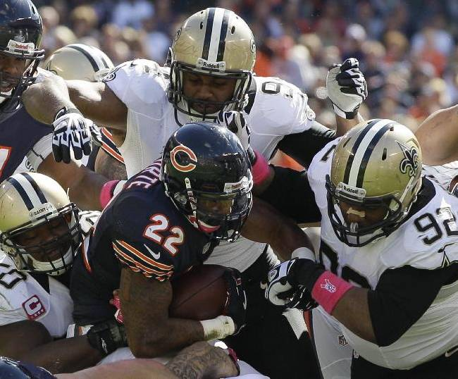 Chicago Bears running back Matt Forte (22) gets tackled by New Orleans Saints middle linebacker Curtis Lofton (50), defensive end Cameron Jordan (94) and nose tackle John Jenkins (92) during the first half of an NFL football game, Sunday, Oct. 6, 2013, in Chicago