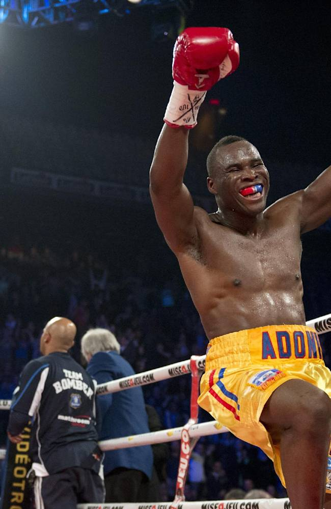 Adonis Stevenson, of Canada, celebrates his victory against Tony Bellew, left, of England, in their WBC light heavyweight title fight in Quebec City early Sunday, Dec. 1, 2013