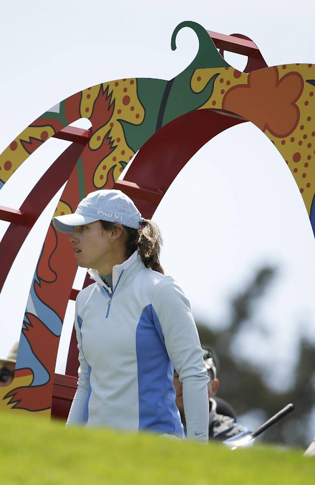 Karin Icher, of France, walks through a Taiwanese sculpture while making her way to the third tee of the Lake Merced Golf Club during the third round of the Swinging Skirts LPGA Classic golf tournament on Saturday, April 26, 2014, in Daly City, Calif