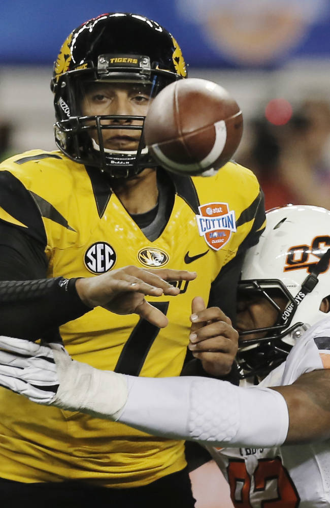 Missouri quarterback James Franklin (1) throws the ball to running back Henry Josey as Oklahoma State defensive end Jimmy Bean (92) defends during the first half of the Cotton Bowl NCAA college football game on Friday, Jan. 3, 2014, in Arlington, Texas. (AP Photo/Brandon Wade)