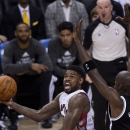 Toronto Raptors forward Amir Johnson, left, shoots as Brooklyn Nets forward Kevin Garnett, right, defends during the second half of Game 2 in an NBA basketball first-round playoff series, Tuesday, April 22, 2014, in Toronto The Associated Press