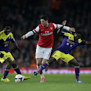 Arsenal's Mikel Arteta, center, competes for the ball with Swansea City's Nathan Dyer, right, and Wilfried Bony during the English Premier League soccer match between Arsenal and Swansea City's at the Emirates Stadium in London, Tuesday, March 25, 2014