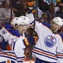 Edmonton Oilers' Mark Fayne celebrates his goal against the Arizona Coyotes with teammates Leon Draisaitl (29) and Benoit Pouliot (67) during the first period of an NHL hockey game Wednesday, Oct. 15, 2014, in Glendale, Ariz The Associated Press