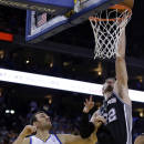 San Antonio Spurs' Tiago Splitter, right, tips in the game winning score over Golden State Warriors' Andrew Bogut (12) during the second half of an NBA basketball game, Thursday, Dec. 19, 2013, in Oakland, Calif. (AP Photo/Ben Margot)