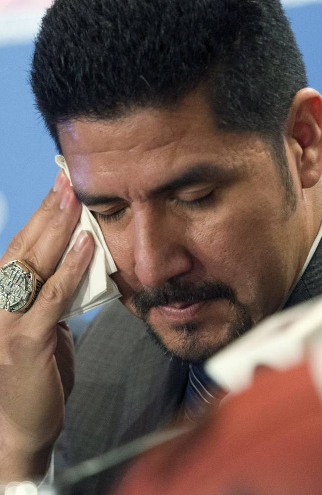Montreal Alouettes quarterback Anthony Calvillo wipes his eye during a news conference announcing his retirement from the Canadian Football League Tuesday, Jan. 21, 2014, in Montreal
