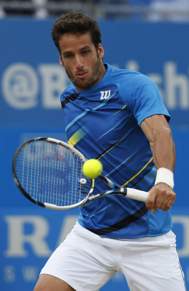Feliciano Lopez of Spain plays a return to Radek Stepanek of the Czech Republic, during their Queen's Club grass court championships semifinal tennis match in London, Saturday, June 14, 2014