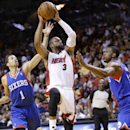 Miami Heat guard Dwyane Wade (3) goes up to shoot against Philadelphia 76ers guard Michael Carter-Williams (1) and forward Thaddeus Young, right, during the first half of an NBA basketball game on Wednesday, April 16, 2014 in Miami The Associated Press