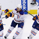 Edmonton Oilers' Sam Gagner (89) celebrates his goal against the Phoenix Coyotes with teammates Matt Hendricks (23) and David Perron (57) during the shootout of an NHL hockey game, Friday, April 4, 2014, in Glendale, Ariz. The Oilers won 3-2 The Associat