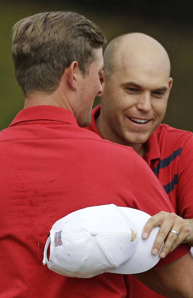 United States' Bill Haas, right, and Webb Simpson celebrate after defeating International's Angel Cabrera, of Argentina, and Branden Grace, of South Africa, 4 and 3 in a fourball match at the Presidents Cup golf tournament at Muirfield Village Golf Club Saturday, Oct. 5, 2013, in Dublin, Ohio