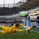 Chelsea's Andre Schuerrle, right, scores past Manchester City's goalkeeper Joe Hart, left, despite the attentions of Eliaquim Mangala during their English Premier League soccer match at the Etihad Stadium, Manchester, England, Sunday Sept. 21, 2014