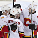 Calgary Flames' Sean Monahan (23), Dennis Wideman (6), Paul Byron (32) and Ladislav Smid (3) celebrate the overtime goal against the Edmonton Oilers during NHL hockey action in Edmonton, Alberta, on Saturday March 1, 2014 The Associated Press