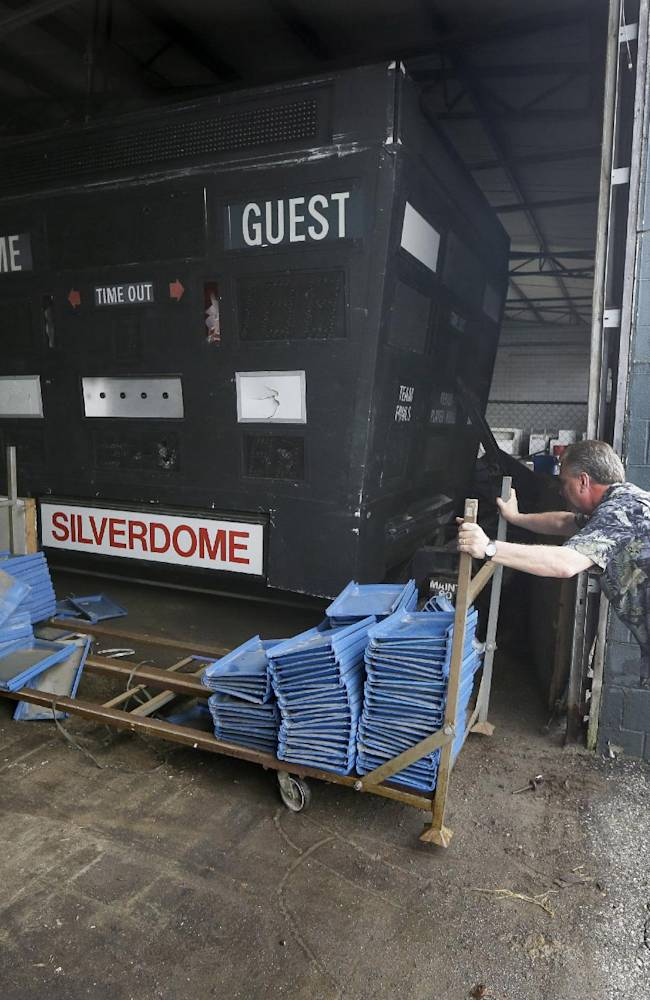 In this Monday, May 12, 2014 file photo, Jim Passeno of RJM Auctions moves a trailer next to a scoreboard in the Pontiac Silverdome, former home of the NFL football Detroit Lions, in Pontiac, Mich. An auction featuring more than 3,000 leftover items in the Pontiac Silverdome has fetched about $500,000. Items up for sale included end-zone turf, pretzel warmers, a boxing ring, a soccer field, flat-screen televisions and scoreboards. The stadium's copper wiring sold for more than $77,000
