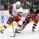 New Jersey Devils' Jon Merrill, right, pokes the puck away from Detroit Red Wings' Darren Helm during the first period of an NHL hockey game Tuesday, March 4, 2014, in Newark, N.J The Associated Press