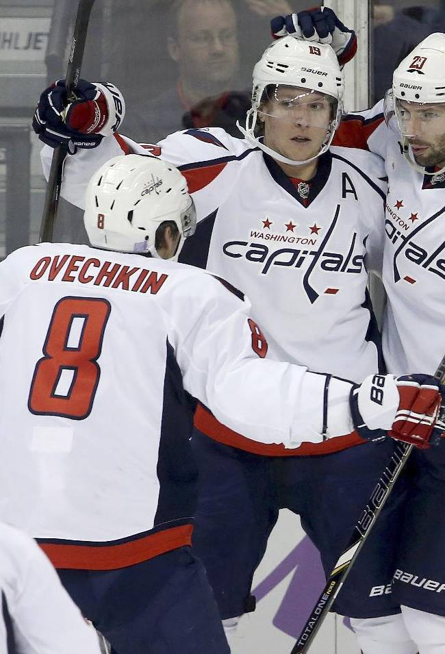 Washington Capitals' Mike Green (52), Alex Ovechkin (8), Nicklas Backstrom (19), and Troy Brouwer (20) celebrate Brouwer's goal during the third period of an NHL hockey game against the Winnipeg Jets in Winnipeg, Manitoba, Tuesday, Oct. 22, 2013