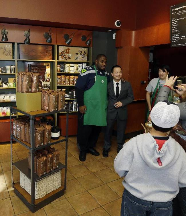 Seattle Seahawks NFL football defensive tackle Brandon Mebane, center, wears a Starbucks green apron as he poses for photos with fans at a Seattle Starbucks store on Wednesday, Oct. 23, 2013, in Seattle. The Seahawks began a one-week fund-raising campaign Wednesday with Starbucks to benefit Seahawks head coach Pete Carroll's A Better Seattle program, which seeks to reach at-risk youth and prevent gang violence