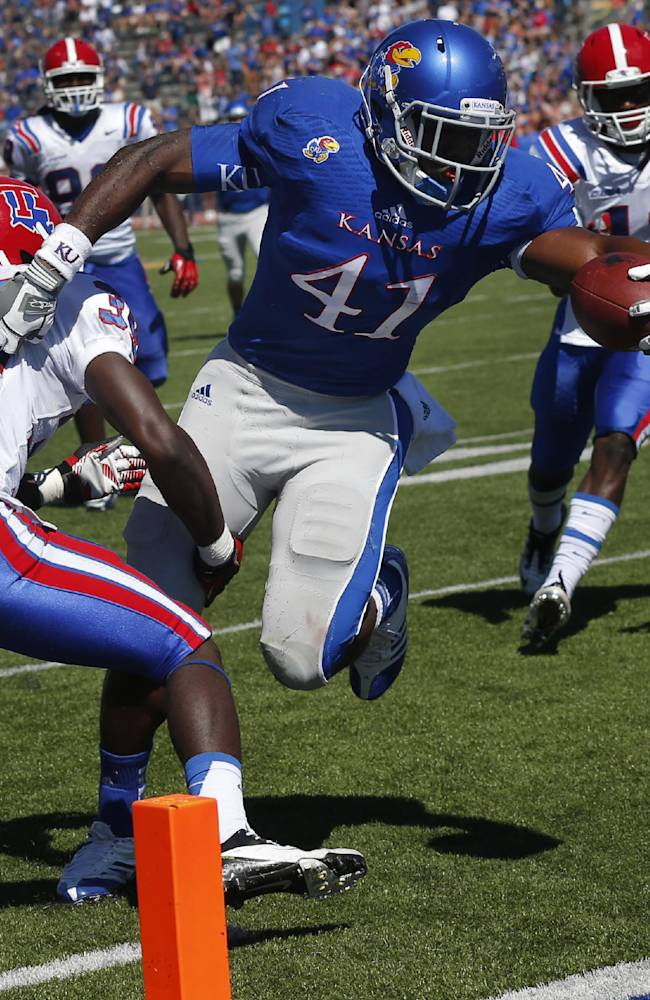 Kansas tight end Jimmay Mundine (41) slips past Louisiana Tech defensive back Xavier Woods (39) for a touchdown during the second half of an NCAA college football game in Lawrence, Kan., Saturday, Sept. 21, 2013. Kansas defeated Louisiana Tech 13-10