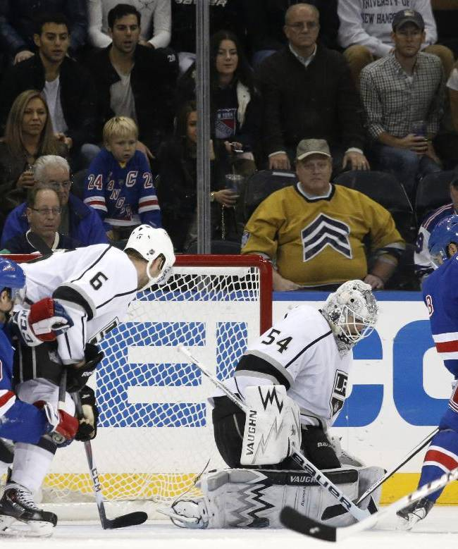 Los Angeles Kings goalie Ben Scrivens (54) blocks a shot by New York Rangers center Dominic Moore (28) with his pads as Rangers center J.T. Miller (10) defends Los Angeles Kings defenseman Jake Muzzin (6) in the third period of their NHL hockey game at Madison Square Garden in New York, Sunday, Nov. 17, 2013.  The Kings shutout the Rangers 1-0. Seconds later Moore thought he scored the tying goal off Scrivens, but after review, it was ruled not a goal because he kicked the puck in with his skate
