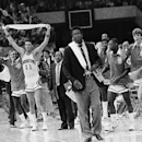 In this March 27, 1982, Georgetown team members wave their arms in victory after they defeated Louisville on Saturday, March 27, 1982, during NCAA men's college basketball tournament semifinals in New Orleans. Coach John Thompson stands in front of them.