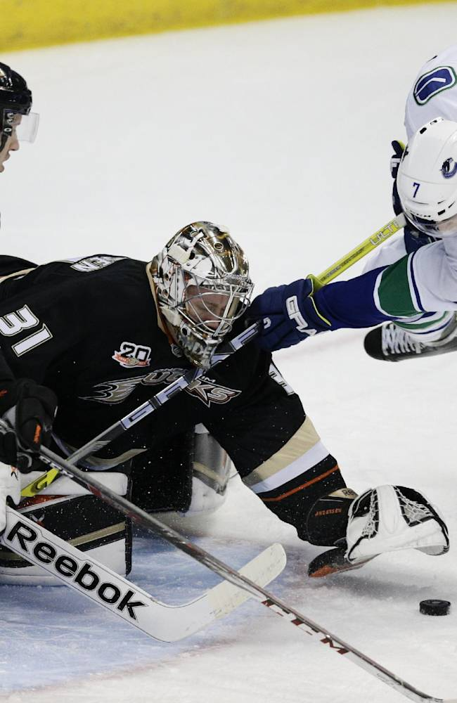Vancouver Canucks' David Booth, right, tries to score against Anaheim Ducks goalie Frederik Andersen, center, of Denmark, as Anaheim Ducks' Nick Bonino watches during the first period of an NHL hockey game on Wednesday, Jan. 15, 2014, in Anaheim, Calif. (AP Photo/Jae C. Hong)