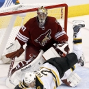 Boston Bruins' Daniel Paille (20) gets tripped up by Arizona Coyotes' Mike Smith (41) during the third period of an NHL hockey game Saturday, Dec. 6, 2014, in Glendale, Ariz. The Bruins defeated the Coyotes 5-2 The Associated Press