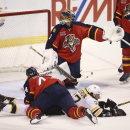 After Florida Panthers' Erik Gudbranson (44) and Boston Bruins' Patrice Bergeron (37) fall to the ice, Panthers goalie Roberto Luongo (1) looks for the puck during the second period of an NHL hockey game in Sunrise, Fla., Sunday, March 9, 2014. Boston Br