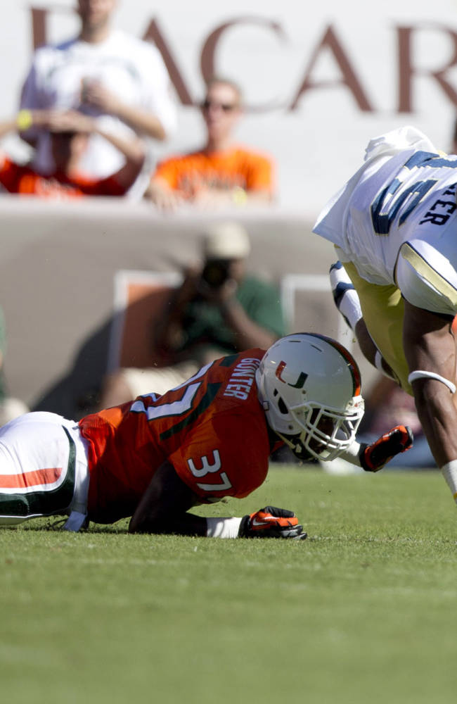 Miami's Ladrius Gunther (37) tackles Georgia Tech's DeAndre Smelter during the first half of an NCAA college football game in Miami Gardens, Fla., Saturday, Oct. 5, 2013