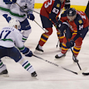 Vancouover Canucks' Radim Vrbata (17) and Florida Panthers' Tomas Fleischmann (14) battle for the puck during the third period of an NHL hockey game in Sunrise, Fla., Monday, Jan. 19, 2015. The Canucks won 2-1 The Associated Press