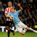 Manchester City's Edin Dzeko is tackled by Sunderland's Wes Brown during the English Premier League soccer match between Manchester City and Sunderland at The Etihad Stadium, Manchester, England, Wednesday, April 16, 2014