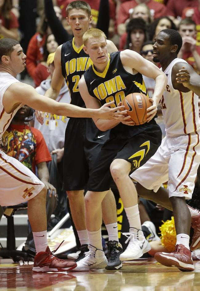 Iowa forward Aaron White, center, looks to pass between Iowa State's Georges Niang, left, and Dustin Hogue, right, during the second half of an NCAA college basketball game, Friday, Dec. 13, 2013, in Ames, Iowa. Iowa State won 85-82