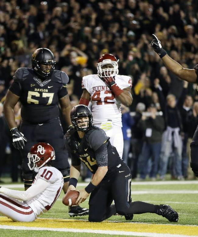 Baylor quarterback Bryce Petty, center, looks down the goal line after scoring on a running play as Desmine Hilliard (67) and Cyril Richardson (68) watch in the first half of an NCAA college football game against Oklahoma, Thursday, Nov. 7, 2013, in Waco, Texas. Oklahoma's Quentin Hayes (10) and linebacker Dominique Alexander (42) watch on the play