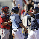 Tampa Bay Rays' Evan Longoria, right, celebrates with teammate David DeJesus, center, as Minnesota Twins catcher Eric Fryer, left, looks on after Longoria hit a two-run home run in the third inning of a spring exhibition baseball game on Sunday, March 2,