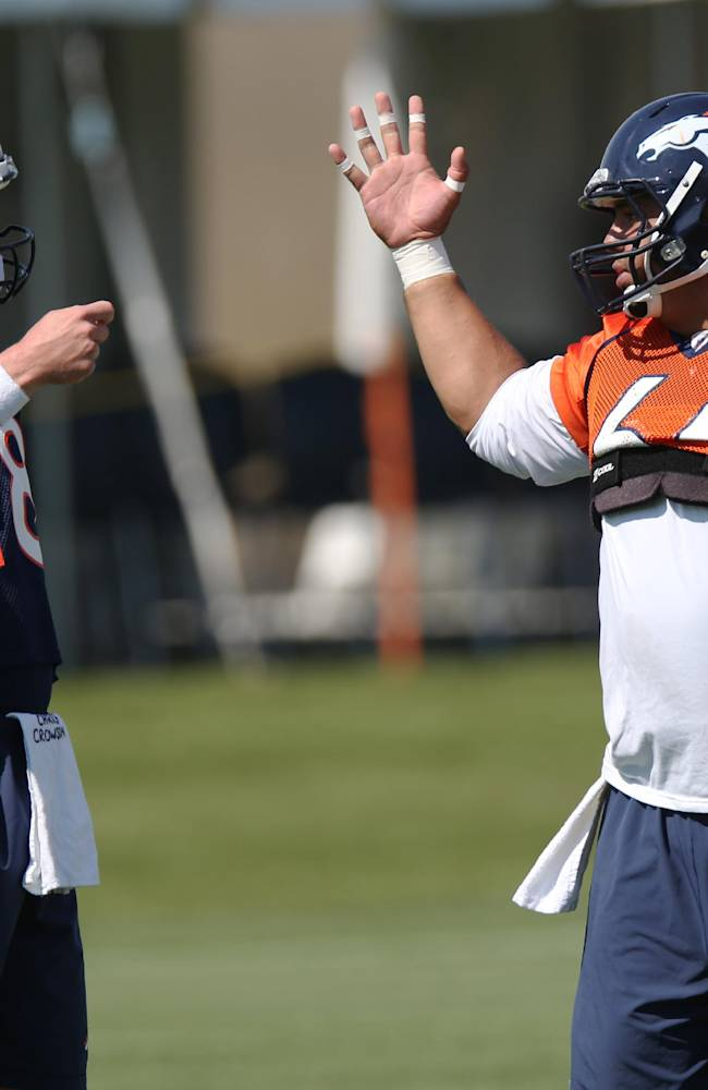 Denver Broncos quarterback Peyton Manning, left, confers with center Manny Ramirez during a morning session at the team's NFL football training camp in Englewood, Colo.,  on Friday, July 25, 2014. (AP Photo)